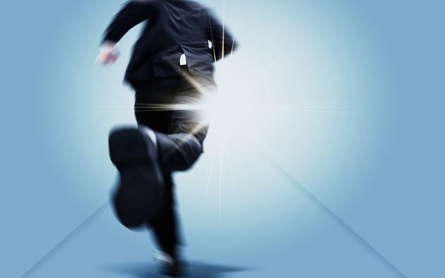 光の射す方向を目指して走るビジネスマン